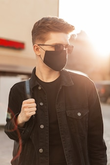 Giovane bell'uomo alla moda con occhiali da sole con zaino e indossa una maschera per l'inquinamento facciale