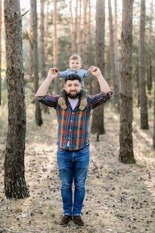 Giovane bel padre e figlio, che indossano abiti casual alla moda, divertendosi nel parco d'autunno