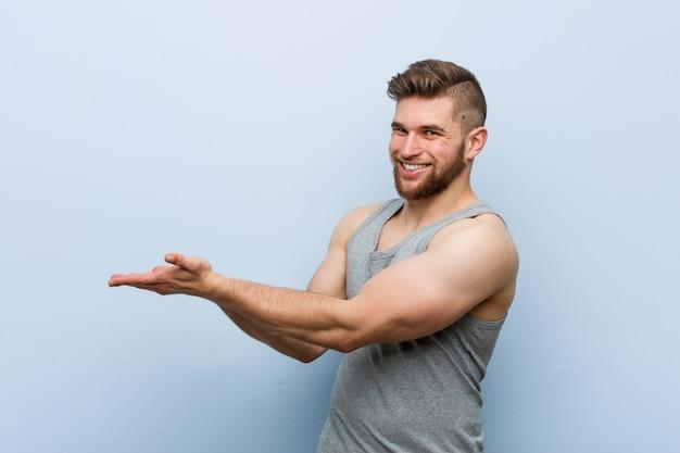 Giovane uomo bello di forma fisica che tiene uno spazio della copia sul palmo.