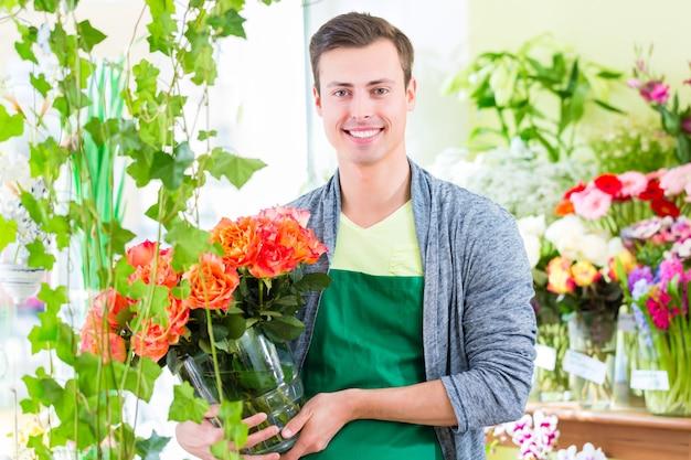 Bel giovane fioraio che vende fiori e mazzi di fiori in negozio