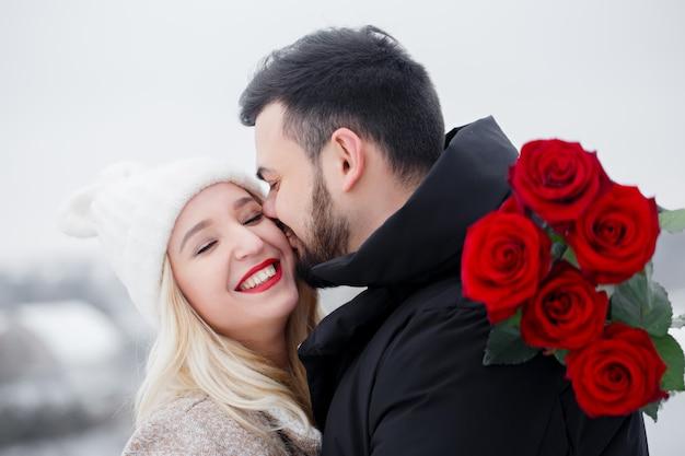 Giovane ragazzo bello che dà a una donna un mazzo di rose il giorno di san valentino