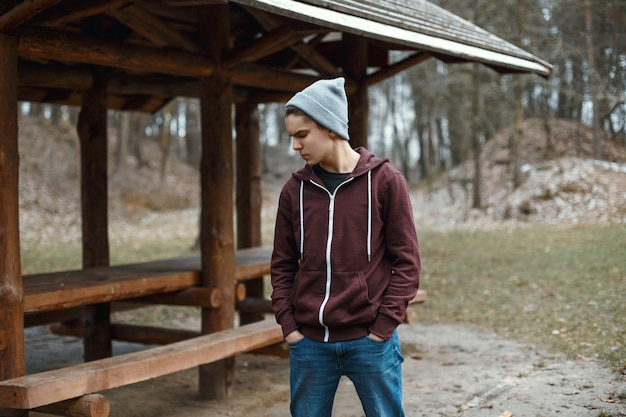 Giovane bel ragazzo in un cappello lavorato a maglia nel parco