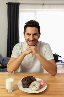 Giovane bel ragazzo si siede a un tavolo e mangia ciambelle.