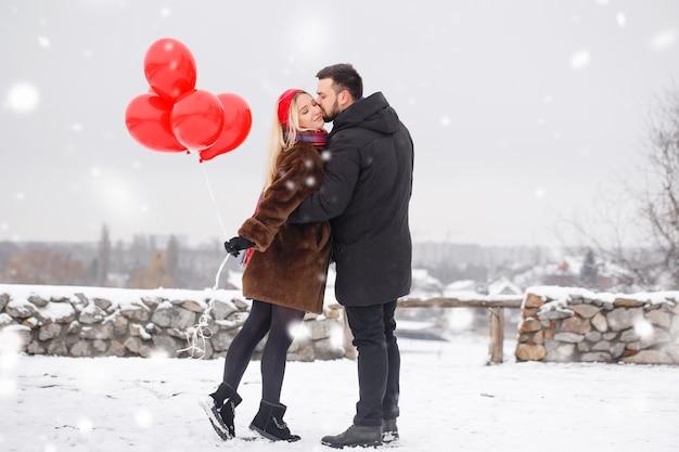 Giovane bel ragazzo e donna con palloncini che camminano il giorno di san valentino