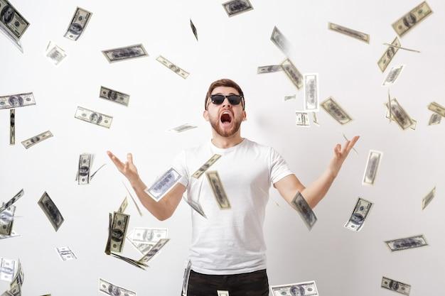 Giovane bell'uomo felice con la barba in una camicia bianca in piedi sotto la pioggia di soldi di banconote da un dollaro