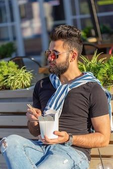 Ragazzo giovane hipster bello mangiare spaghetti cinesi da un pranzo al sacco mentre era seduto su una panchina del parco