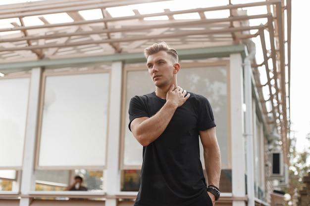 Ragazzo giovane hipster bello con acconciatura in maglietta nera alla moda passeggiate in città