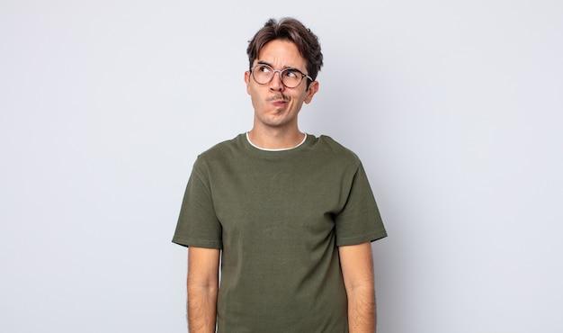 Giovane bell'uomo ispanico che sembra perplesso e confuso, chiedendosi o cercando di risolvere un problema o pensando