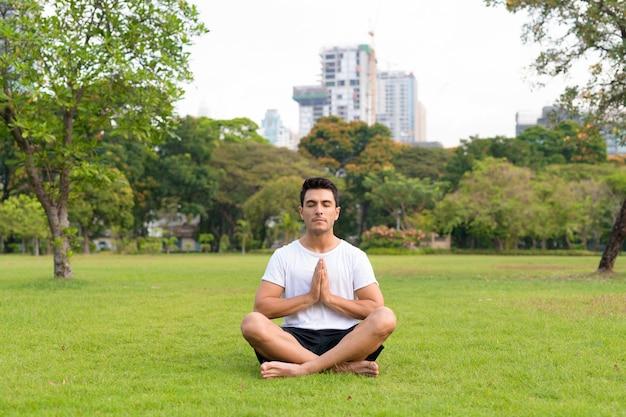 Giovane uomo ispanico bello che medita con gli occhi chiusi al parco