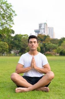 Giovane uomo ispanico bello che medita con le mani giunte al parco