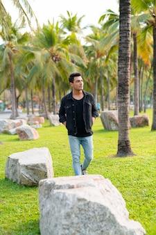 Giovane uomo ispanico bello pensare mentre si cammina al parco