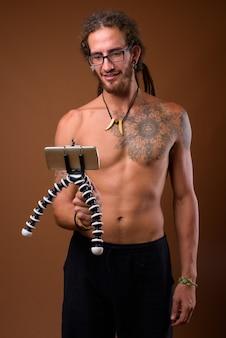 Giovane uomo ispanico bello con i dreadlocks a torso nudo contro br
