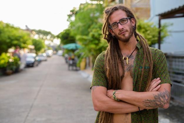 Giovane uomo turistico ispanico bello con i dreadlocks nella strada