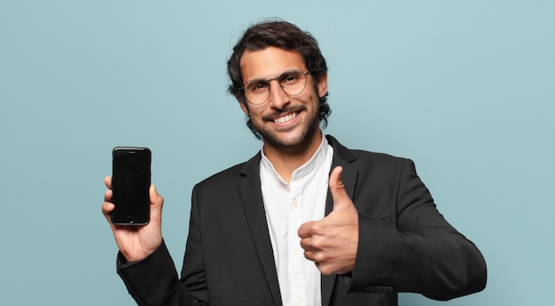 Giovane uomo d'affari indiano bello che mostra il suo schermo vuoto del telefono