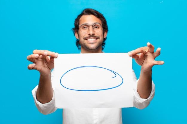 Giovane uomo d'affari indiano bello che mostra un foglio di carta di osservazione
