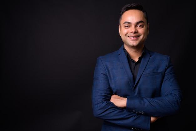 Bel giovane uomo d'affari indiano che indossa tuta blu contro il muro nero