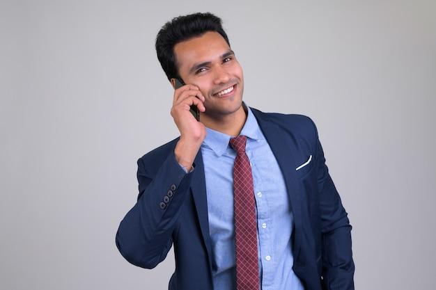 Giovane uomo d'affari indiano bello che porta vestito su bianco