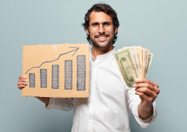 Giovane uomo d'affari indiano bello con banconote e un grafico a barre