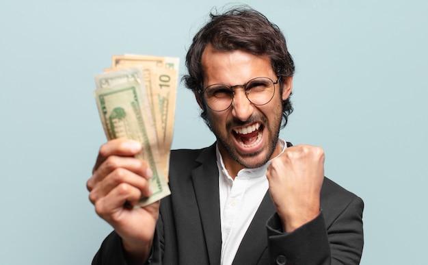 Giovane uomo d'affari indiano bello con le banconote