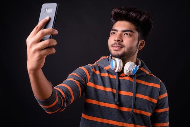 Bel giovane uomo indiano su sfondo nero Foto Premium