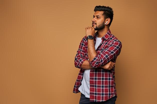 Giovane uomo indiano bello in chiusura casual con le braccia incrociate sul muro pastello