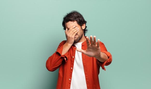 Giovane uomo indiano bello che copre il viso con la mano e mette l'altra mano davanti per fermare la fotocamera, rifiutando foto o immagini