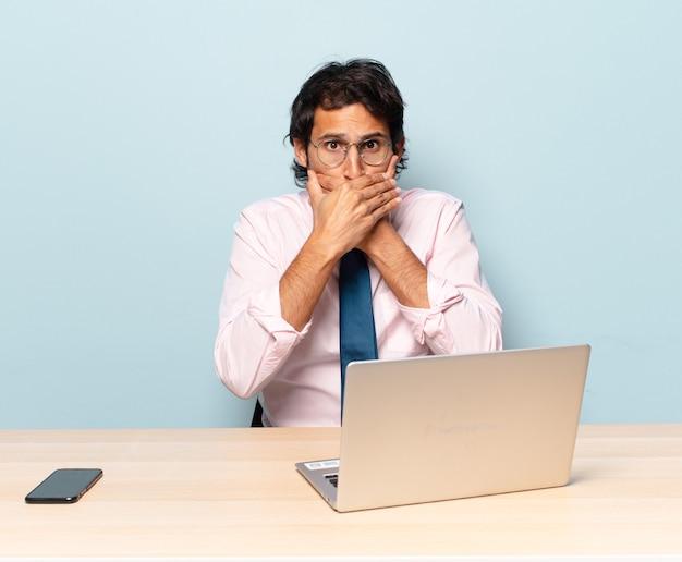 Giovane uomo indiano bello che copre la bocca con le mani con un'espressione scioccata e sorpresa, mantenendo un segreto o dicendo oops. concetto di business e freelance