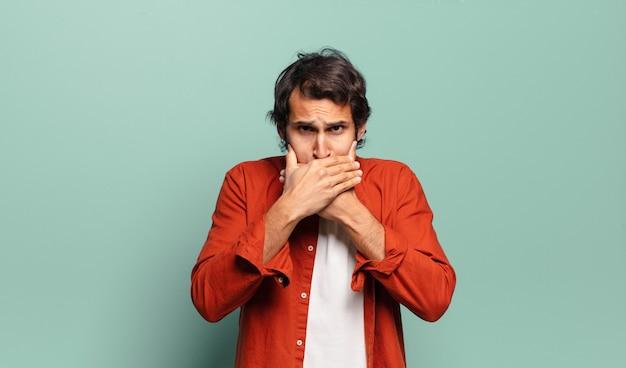 Giovane uomo indiano bello che copre la bocca con le mani con un'espressione scioccata e sorpresa, mantenendo un segreto o dicendo oops