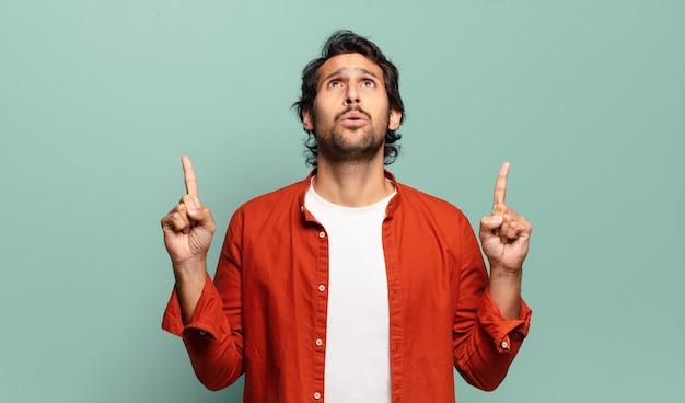 Giovane uomo indiano bello che si sente intimorito e a bocca aperta rivolto verso l'alto con uno sguardo scioccato e sorpreso