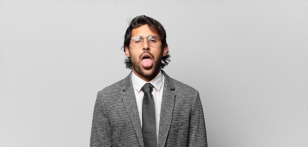 Giovane bell'uomo indiano che si sente disgustato e irritato, tira fuori la lingua, non ama qualcosa di brutto e schifoso. concetto di business