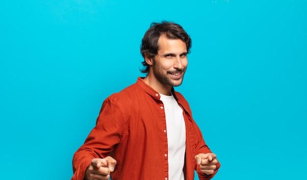 Giovane bell'uomo indiano che si sente felice, freddo, soddisfatto, rilassato e di successo, punta davanti, sceglie te