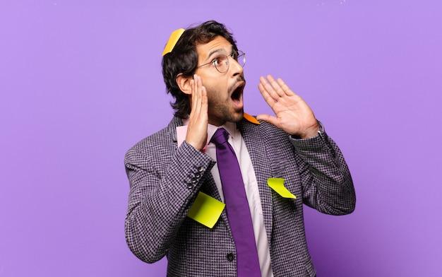 Giovane uomo indiano bello che si sente felice, eccitato e sorpreso, guardando al lato con entrambe le mani sul viso. concetto di business umoristico