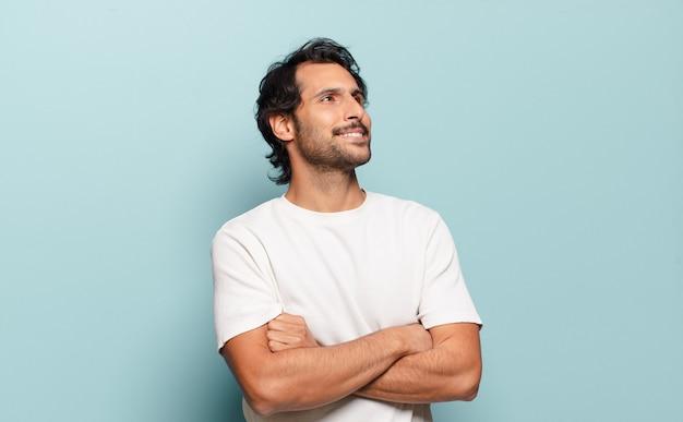 Giovane uomo indiano bello che si sente felice, orgoglioso e speranzoso, chiedendosi o pensando, alzando lo sguardo per copiare lo spazio con le braccia incrociate