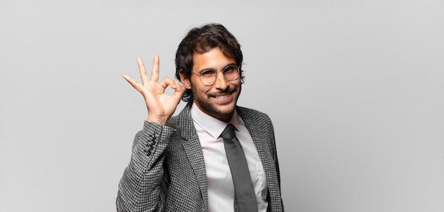 Giovane uomo indiano bello che si sente felice, rilassato e soddisfatto, mostrando l'approvazione con il gesto giusto, sorridendo