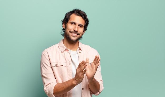 Giovane uomo indiano bello che si sente felice e di successo, sorride e batte le mani, congratulandosi con un applauso