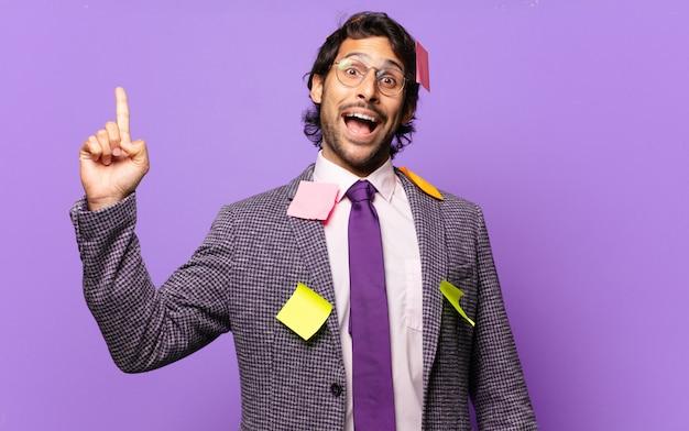 Giovane uomo indiano bello che si sente come un genio felice ed eccitato dopo aver realizzato un'idea, alzando allegramente il dito, eureka !. concetto di business umoristico