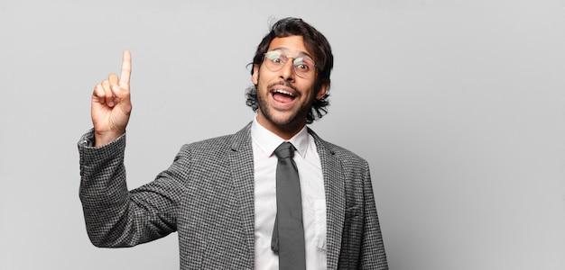 Giovane bell'uomo indiano che si sente come un genio felice ed eccitato dopo aver realizzato un'idea, alzando allegramente il dito, eureka!