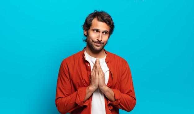 Giovane uomo indiano bello che si sente orgoglioso, malizioso e arrogante mentre trama un piano malvagio o pensa a un trucco
