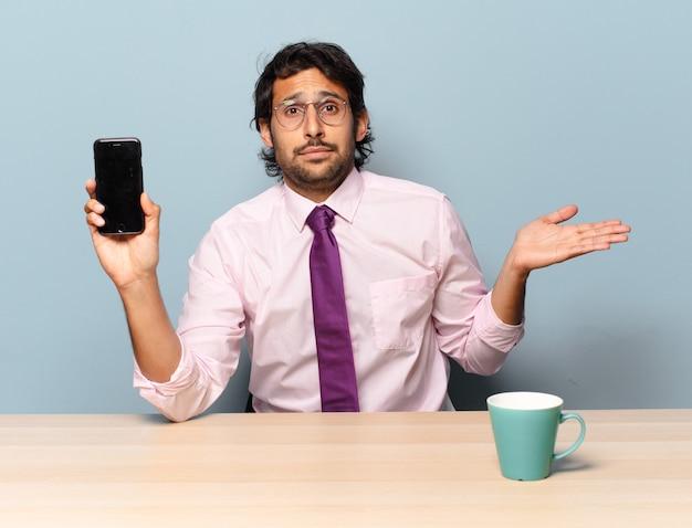 Giovane uomo indiano bello sentirsi perplesso e confuso, dubitare, ponderare o scegliere diverse opzioni con un'espressione divertente. concetto di affari