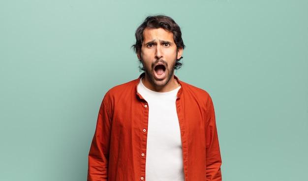 Giovane uomo indiano bello che si sente terrorizzato e scioccato, con la bocca spalancata per la sorpresa