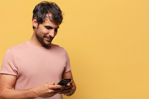 Giovane bell'uomo indiano. concetto di smartphone espressione felice e sorpresa