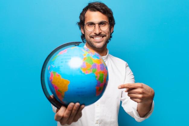 Giovane uomo indiano bello che tiene il globo della terra