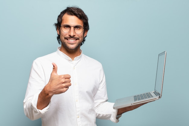 Giovane uomo indiano bello che tiene un computer portatile. concetto di business o social media