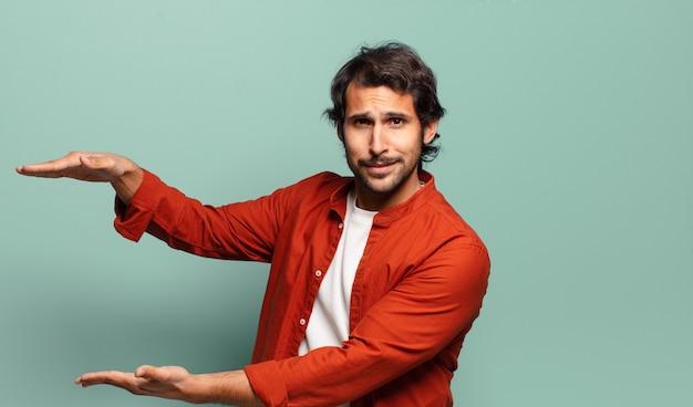 Giovane uomo indiano bello che tiene un oggetto con entrambe le mani sullo spazio della copia laterale, mostrando, offrendo o pubblicizzando un oggetto