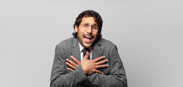 Giovane uomo indiano bello che ride ad alta voce a uno scherzo esilarante, sentendosi felice e allegro, divertendosi. concetto di affari