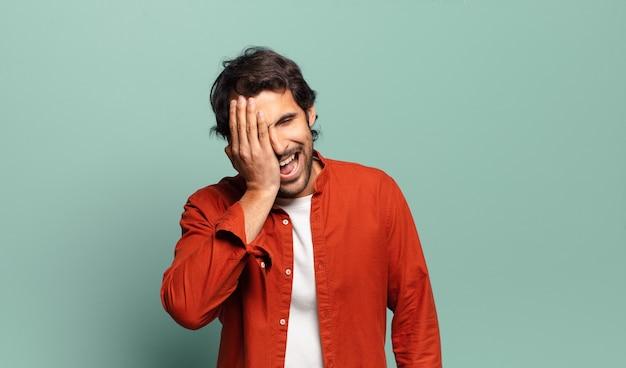 Giovane uomo indiano bello che ride e che schiaffeggia la fronte