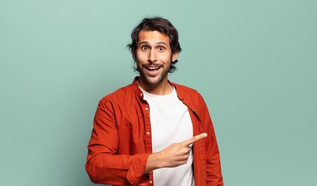 Giovane uomo indiano bello che sembra eccitato e sorpreso che punta di lato e verso l'alto per copiare lo spazio