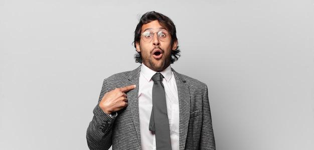 Giovane uomo indiano bello che sembra scioccato e sorpreso con la bocca spalancata, indicando se stesso. concetto di affari