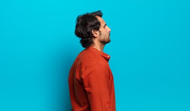 Giovane uomo indiano bello sulla vista di profilo che cerca di copiare lo spazio davanti, pensare, immaginare o sognare ad occhi aperti