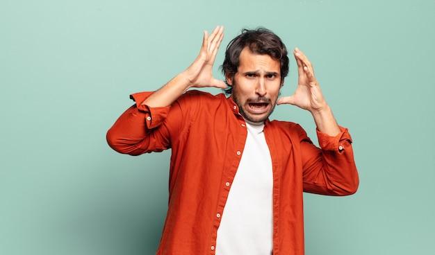 Giovane uomo indiano bello che grida con le mani in aria, sentendosi furioso, frustrato, stressato e sconvolto